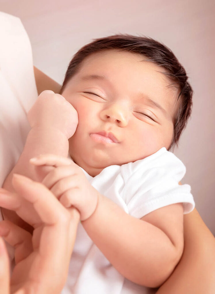 Een slapende baby in mama's armen