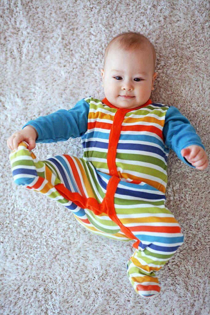 6 maanden oude baby die zijn beentje strekt