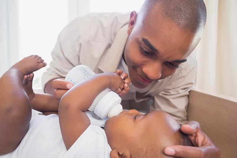 Trotse pappa die liefdevol zijn pasgeboren zoon voedt met een flesje melk