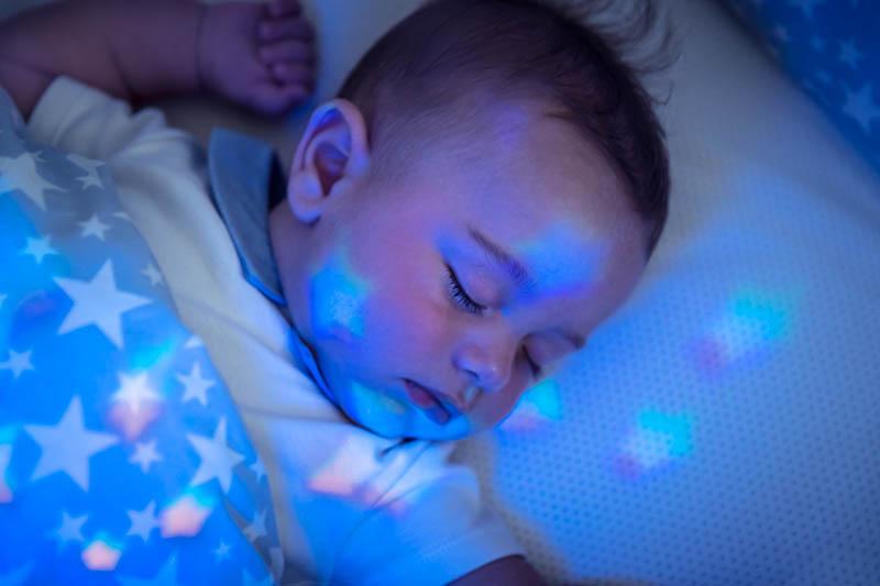Een baby die ligt te slapen met een stervormig nachtlampje