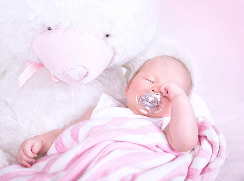 Pasgeboren baby met speen in de mond