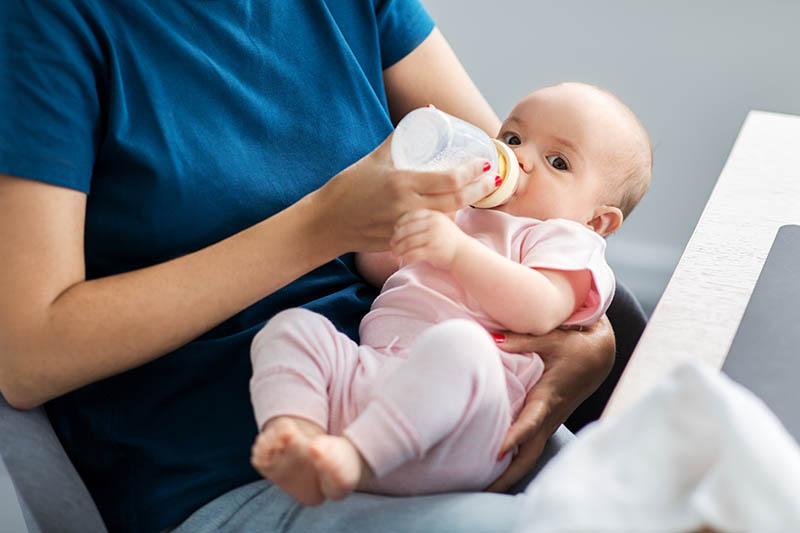 Een moeder die haar pasgeboren baby voedt met melk uit de fles