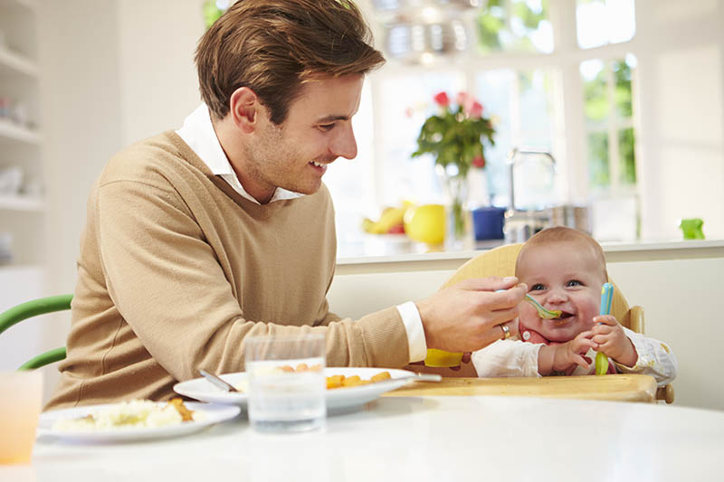 Trotse papa die zijn dochter met een lepel aan tafel voedt