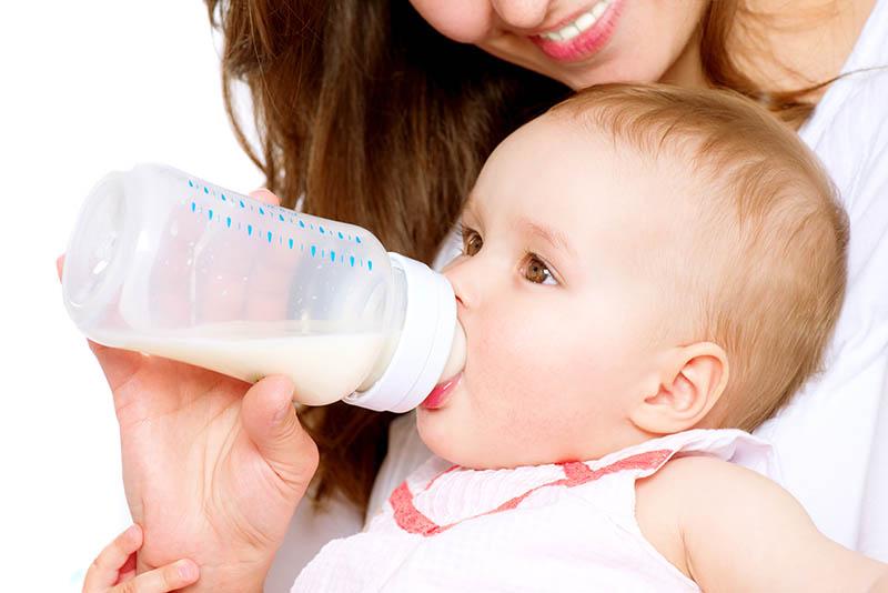 Moeder die haar baby liefdevol een flesje melk voedt