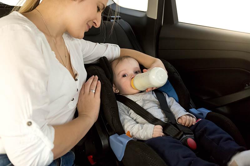 Moeder die haar pasgeboren zoon een flesje melk voedt in de auto