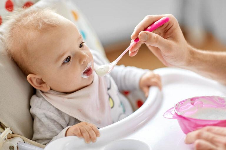 Vader voedt baby met lepel die thuis in de kinderstoel zit | Voedingsschema baby